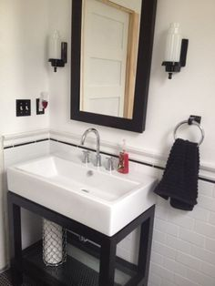 After picture: Sink and medicine cabinet from Restoration hardware, sconces, switchplates, and towel ring from Rejuvenation, white subway tile with black pencil trim from The Tile Shop