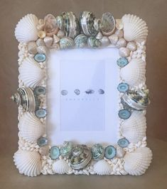 Shell Photo Frame topped with lovely large green and pearlised striped turbo shells. Studded with pearlised trochus seashells and small abalone. Highlighted on the sides with white clam shells, green limpet shells and encrusted with white nassa shells. This 100% handmade, custom shell picture frame Seashell Frame, Seashell Crafts, Beach Gifts, Shell Jewelry, Green Stripes, Coastal Decor, Sea Shells, Picture Frames, Eagle Creek