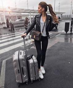 Iva Nikolina Juric wears a V neck top, black jeans, and a classic leather jacket to create this sleek travel-ready style. Sneakers are essential for comfort and ease when travelling! Brands not specified.
