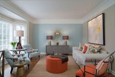 Complementary colors work wonders! A soft blue and a bold orange are the palate in this Contemporary Living Room by Beckwith Interiors