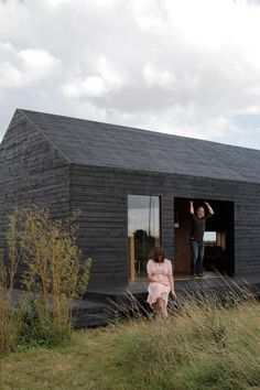 30 All-Black Exterior Modern Homes - Photo 16 of 30 - Carl Turner and Mary Martin pose on the porch of the Stealth Barn, a multipurpose structure that plays as a guest cottage, office space, and escape from whatever may be cooking at Ochre Barn. Modern Exterior, Exterior Design, Black Exterior, Exterior Paint, Exterior Colors, Casa Bunker, Norfolk England, Norfolk County, Casas Containers
