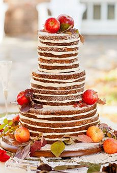 Bare cake layers with creamy frosting topped with fresh apples. Fantastic fall wedding cake!