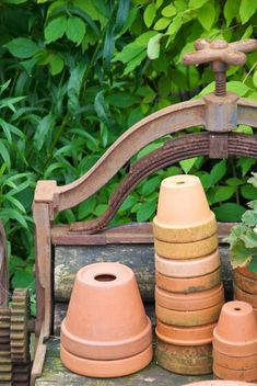 Terra cotta pots stacked on an old piece of machinery. Not sure what it is, but lovely.