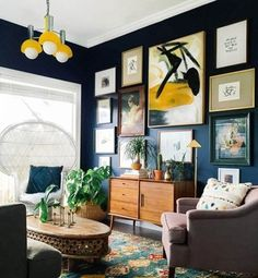 How to create a gallery wall and display art in your home. Art prints look great against a dark painted wall as in this eclectic bohemian living room. Gallery wall on dark blue wall. Read our feature for more tips on how to use art in your home.