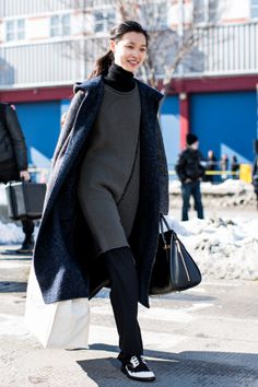 Winter Outfit Idea - black turtleneck under a grey mini dress worn over black trousers + sneakers and a cozy winter coat | StyleCaster