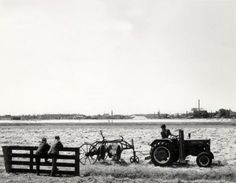 Landbouwtractoren. Een boer bewerkt zijn land met een tractor met maaibalk, en daarachter een harkkeerder, terwijl twee mannen leunend tegen een hek hem gadeslaan. Op de achtergrond de rand met industriegebouwen van een stad,  Nederland 1961.