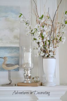 Summer beachy mantel with water print, sand filled candleholders, coral, water birds, and white urns with manzanita branches ( I'd add beach grass...)