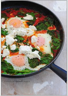 cumulus spiced eggs by jules:stonesoup, via Flickr  Ingredients: 1 jar tomato pasta sauce (about 1 1/2 cups)  1-2 teaspoons ground coriander  4 handfuls baby spinach leaves  4 eggs  small handful soft goats cheese.  Method: Warm sauce and spice in frying pan. Add spinach and stir for a minute. Make 4 indents and crack an egg into each. Cover frying pan with a lid for 4 minutes or until eggs are gently cooked. Crumble over goats cheese and season with salt and pepper. Serve!