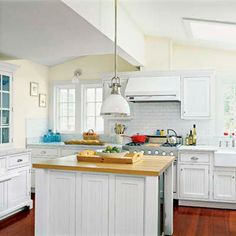 A white enamel finish on the modern range and vent hood allow these appliances to fit in with the vintage look of the room. | Photo: Julian Wass | thisoldhouse.com