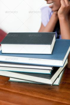 Stack of books on a table ...  academic, adult, afro-american, attractive, beautiful, book, books, class, college, confidence, cute, desk, determination, education, exam, female, girl, home, homework, knowledge, learn, learning, library, one, pen, people, person, portrait, read, school, schoolwork, serious, smart, smile, smiling, stack, student, study, studying, success, teen, teenage, teenager, test, text, university, woman, writing, young, youth