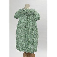 Little girl's dress, 1930, (rear view) of unlined cotton lawn printed with a design of stylized flowers and foliage in green and blue on a white ground. The dress has a round neck with a turn-down collar of white lawn, and puffed sleeves gathered into a frill above the hem. The upper part of the dress is decorated with hand embroidery in powder blue and olive green threads. The chest and back of the dress are smocked in blue and green.