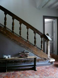 Rustic entryway with old wooden staircase banister, hexagon tile floor, and a vintage bench.