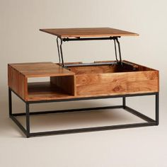 Richly grained acacia wood on a sleek metal base - there's more to this clever coffee table than meets the eye. Disguised as a drawer with a mid-century-style cutout handle, one side of the tabletop lifts up to reveal storage space for media accessories, and it can be extended into a laptop-friendly work surface. A small open cubby compartment keeps magazines and remotes accessible yet tidy.