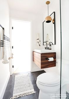 Loving this small, modern bathroom design. Brass pendant / floating wood sink / black hardware / dark grey hexagon tiles. via @thehomely