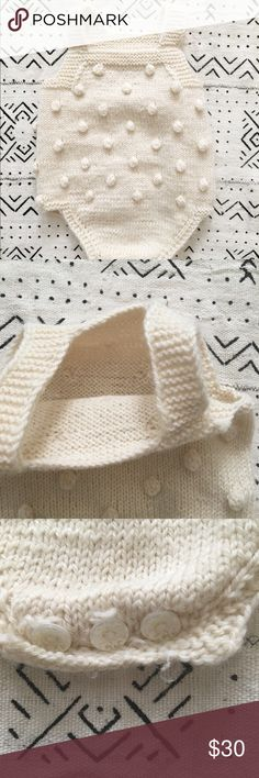 Handknit Ivory baby romper 6-9 months This is a handmade pom pom bubble romper with a button closure at the bottom.  It is made of an acrylic blend yarn and does not have a size tag but fits Up to 9 months.  I had someone make this for photos but never ended up using because I had a big baby so the season didnt quite line up.   It is soft and the little buttons have a little bit of a print on them.  Great for unisex. One Pieces Bodysuits