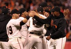 The Giants, including Marco Scutaro (19) shaking hands with Francisco Peguero, celebrate their National League West division title after defeating the Padres.
