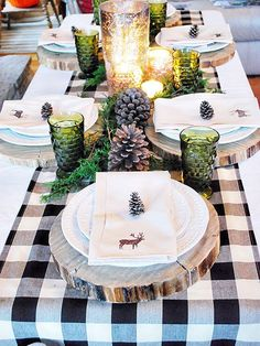 green glass candle holders, pinecones, wood slice chargers and greenery