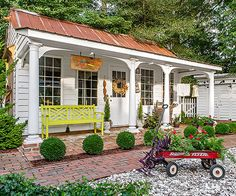 This large shed looks like anything but a storage unit. Its copper roof, welcoming porch and colorful bench make it a true extension of the home.