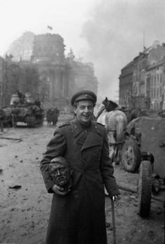 A Soviet soldier with the head of a statue of Hitler, Berlin, 1945