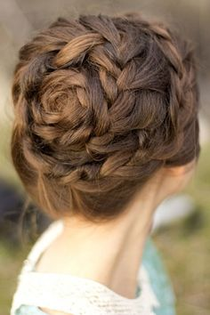 A delicate hairstyle that is a spiral of braids with a center that looks like a rose - Photo Credit: Hair and Makeup by Steph