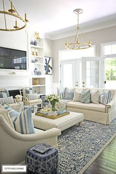 Summer decorated living room with blue and white, brass and stripes. Layered pil… Summer decorated living room with blue and white, brass and stripes. Layered pillows in mixed patterns for a relaxed, coastal feel. Coastal Living Rooms, Home Living Room, Living Room Designs, Hamptons Living Room, Barn Living, Classic Living Room, Blue And White Living Room, Blue Living Room Decor, Living Room Ottoman Ideas