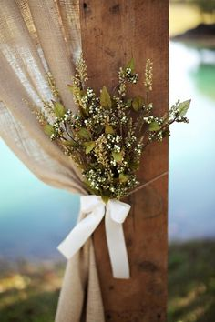 Burlap drape with floral accent, with wooden beam.