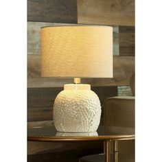 Breathe new life into your favorite room with this Table Lamp by StyleCraft. A white ceramic base adds sturdiness, while the 3D pattern brings gorgeous texture to this striking accent lamp. A cylindrical shade in a light beige color tops off the versatile neutral look, which looks perfect in any room of the house.