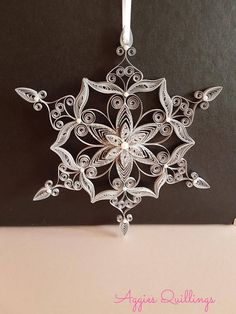 Quilled silver snowflake Christmas tree decoration with glitter and pearls. Comes in its own box with a satin ribbon, ready to use on your Christmas tree. Great gift idea for a special someone :) Size: H 16cm W 16cm Please handle with care, this quilling is extra delicate.