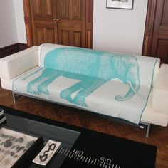 chic cream-colored couch covered in blue elephant blanket
