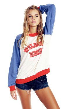 Wildfox High. This sweater is totally 80's-inspired with red hems, blue raglan-style sleeves, and 'Wildfox High' in red flocking across the front. Scoop neck. Banded hems. A roomy fit hangs off the body in a light, and slightly distressed, Irish terrycloth blend. 85% Cotton, 15% Polyester  Model wears a size small.