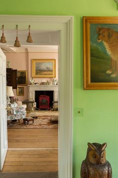 A view to the drawing room from the vibrant green hall. A trio of passementerie tassels adds jollity to the doorway.