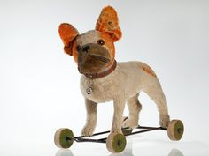 """Steiff  """"Bully"""" on wheels with connecting frame (1335,2 / series 11)  Mohair plush white/gold (= orange)  Swivel head and pull voice  Leather and horse hair collar with bell  11 Steiff buttons in total – one in the ear and 10 on the collar  Maker's height: 35 cm (without wheels)"""