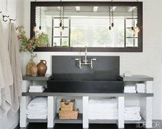 Actress Meg Ryan created a relaxed oasis with the help of decorator Marsha Russell  for her Martha's Vineyard master bath. An antique soapstone sink basin from LooLoo Design is set into a bluestone countertop with painted-brick supports; the pendant lights are vintage, and a framed mirror anchors the space. Tour the rest of this house.   Photographer: William Waldron  - ELLEDecor.com