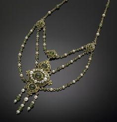 An arts & crafts cultured pearl, demantoid, enamel and fourteen karat gold necklace, Marcus & Co. the triple swag necklace designed with a central plaque of champlevé enamel, with demantoid garnet beads, framed by button and seed pearls, completed by chains set with demantoid beads and pearls; signed Marcus & Co