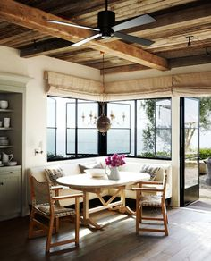 Breakfast nook with exposed beams and built in banquette seating. Casement windows