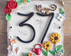 This beautifully hand made ceramic house sign is personalised with your own house number. I can replicate the design above with your cats, roses, a wee watering can and sunflowers or you can choose your own characters, colours and features! Pottery Houses, Slab Pottery, Clay Houses, Ceramic Houses, Ceramic House Numbers, English Garden Design, Clay Magnets, Sunflower Party, 3rd Grade Art