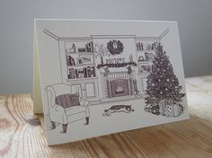 Christmas card features illustration of cat sleeping in front of festive decorated fireplace.