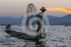A leg rowing fisherman on Inle Lake in Shan State in Myanmar (Burma).This unique style of rowing evolved because the shallow lake bottom is covered by reeds and plants making it difficult to see the fish while sitting.