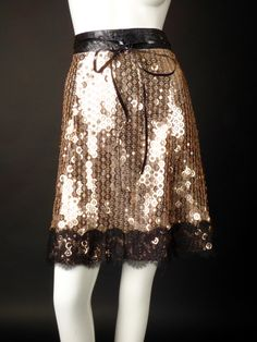 Wonderful little party skirt in silk organza and covered in gold circle paillettes and with square sequins in the centers. The skirt is a-line shape and has a black crinkle vinyl waistband with a stri