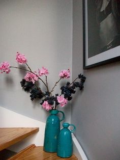 flowers in turquoise vases by Abigail Ahern, grey paint by Dulux in Chic Shadow. a beautiful mid grey colour, ideal for hallway, staircase stairwell. Chanel posters.
