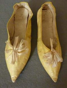 Lemon yellow kid leather slippers, c. 1790's. With elongated pointed toes, cream silk looped ribbon decoration, and forward slanting side seams. The top edges and back seams are all bound with silk ribbon. Low shaped lemon leather heels and brown leather straight soles. Lining of slightly glazed linen.