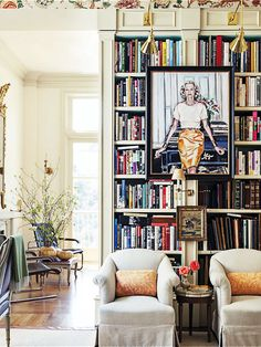 painting on bookshelf, chairs, table, lighting on bookshelf