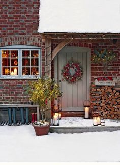 I love all of this.  The warm glow from the window, the snow boots in a row, the piled up firewood, the lights and the wreath.  Lovely.