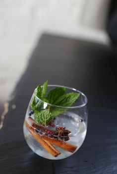 Add gin and tonic to a glass over large ice cubes. Add large mint sprig, cinnamon sticks, star anise, orange zest, juniper berries and pink peppercorns to glass.