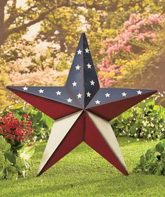 """Put the 24"""" Americana Star Decor on display all year long in your home or garden. The large-scale barn star is decorated with an American-themed design, perfect for outdoor use. Use the 7"""" stakes to install it into the ground, or use the included jute ro"""