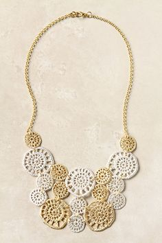 This could be an easy DIY neckalce. Find a pretty lace pattern, cut out the detail, coat it with metallic paint, and piece together with jewelry rings.
