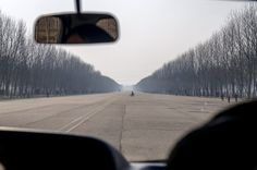 Hero Youth Highway from Pyongyang to Nampo, a city on the west coast of the peninsula, 2012. Many of the highways in North Korea are like this, massive, straight and empty, often going straight through mountains. (Eric Testroete)