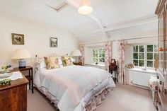 A charming bedroom in soft pinks and grey with lots of old world characterin deep-set  windows and exposed beams