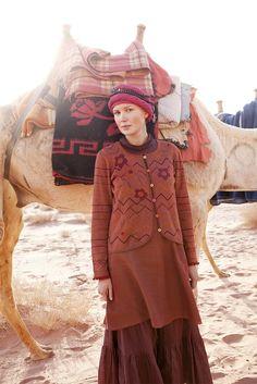 """rote Strickjacke 'Wadi':  Das Model trägt eine rote Stickjacke aus Baumwolle, die mit einem gleichfarbigen Trägerkleid kombiniert ist. Das Foto wurde in der jordanischen Wüste """"Wadi Rum"""" mit einem Kamel von Beduine Mohammad gemacht."""