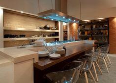 Elaborado por Tufi Mousse, o ambiente de 67m² mistura a estética dos anos 1940 com a tecnologia atual, apostando em paredes revestidas em quartzo, piso vinílico e marcenaria sob medida em tons de cinza.